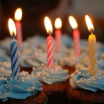 Cupcakes with blue frosting, white sprinkles, multicolored lit candles