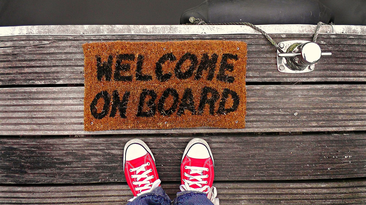 feet on the edge of a dock with a welcome mat that says welcome on board
